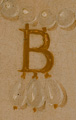 Detail 04. Detail of the monogram pendant.