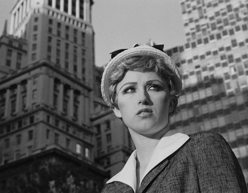 Cindy Sherman posing near buildings