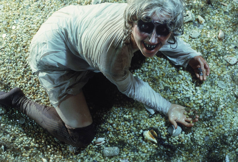 Cindy Sherman film still with makeup posing in pebbled floor