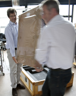 The painting being moved from its crate to be unpacked
