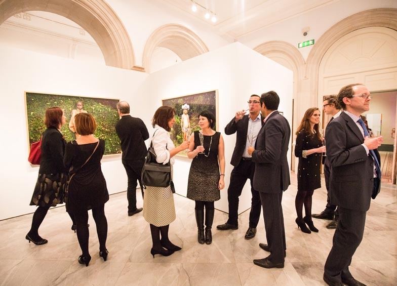 Patrons viewing works of art in private view