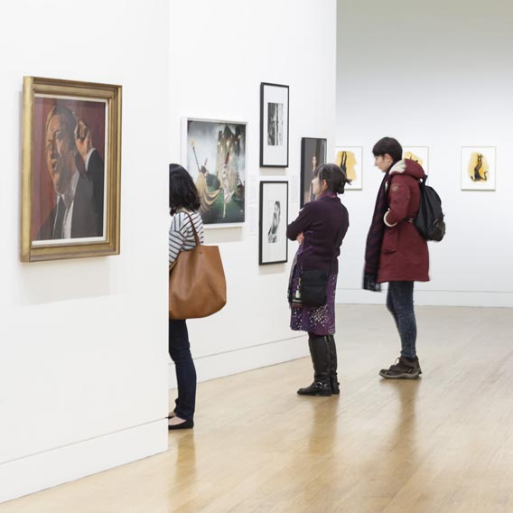 Make a donation, people enjoying the 20th century portraits in the Gallery