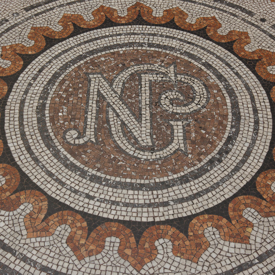 Mosaic Supporter, original mosaic logo on floor of Gallery